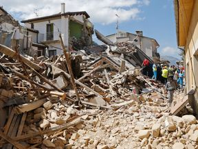 People and rescuers stand next collapsed buildings following an earthquake in Amatrice, central Italy
