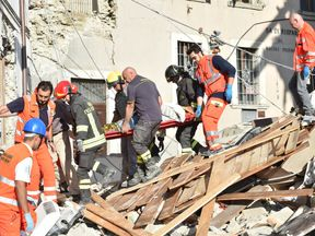 Rescuers clear debris while searching for victims in damaged buildings in Arquata del Tronto, Italy