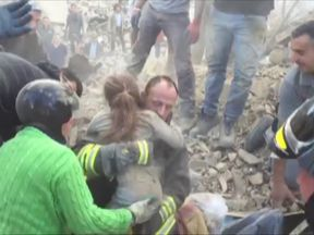 The rescuer clutches the girl to his chest after she was pulled from the rubble