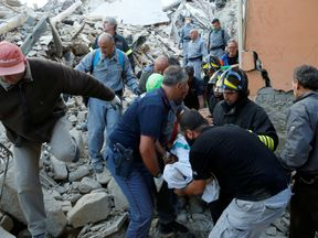 Rescuers carry a person on a stretcher in Amatrice