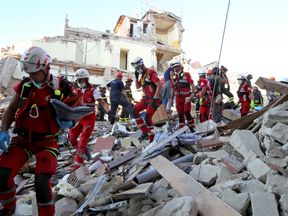 Rescuers walk through rubble following the earthquake in Amatrice,