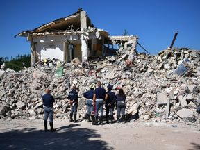 Emergency workers survey the scene of the collapsed building in Amatrice