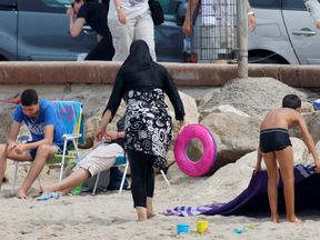 A Muslim woman wears a burkini on a beach in Marseille, France (library pic)
