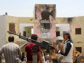 Yemeni security forces stand guard at the site of a suicide car bombing
