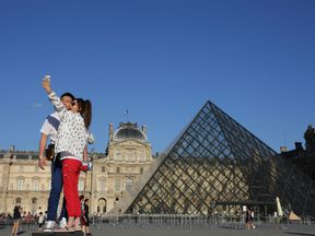 Tourists take a selfie in front of the Louvre pyramid in Paris