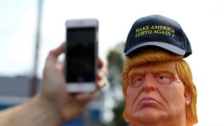 A passerby takes a picture of a statue depicting republican presidential nominee Donald Trump in the nude in San Francisco