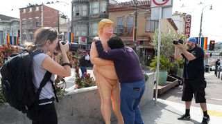 A passerby hugs a statue depicting republican presidential nominee Donald Trump in San Francisco