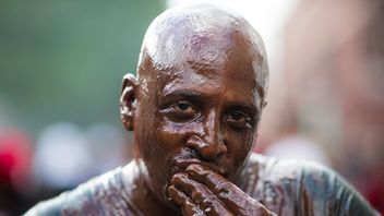 A man wears a wet look for as part of his costume