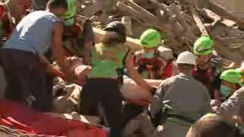 A woman is pulled alive from the rubble