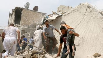 A Syrian man carries a wounded child after a barrel bomb attack on  Aleppo