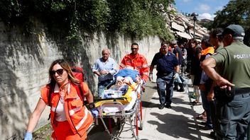 An injured person is carried away on a stretcher following an earthquake at Pescara del Tront