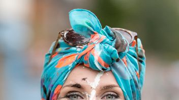 A woman with a bright-blue headscarf and paint-covered face flashes a big smile