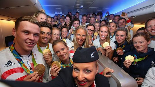 A crew member uses a selfie stick to take a photo with Team GB medal winners