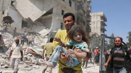 An Aleppo man carries a child after the regime reportedly dropped barrel bombs