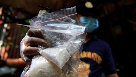 A Filipino officer displays confiscated methampthetamine seized during a raid in Manila