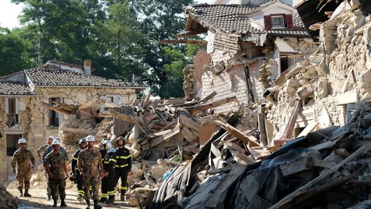 Firefighters and soldier walk through ruins during an operation to reopen a road in Rio, a village near Amatrice