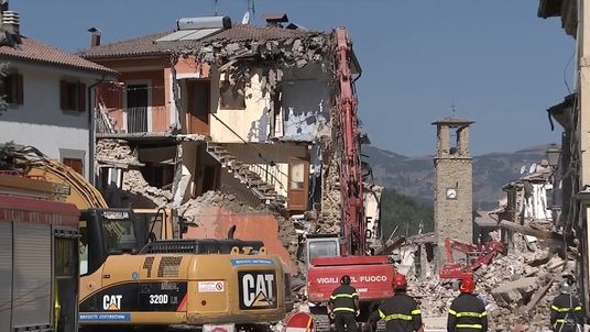 A crane demolishes a house which was damaged by the earthquake
