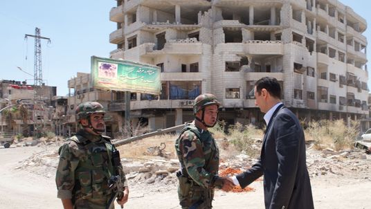 President Assad (R) shakes hands with soldiers in the Darya area in 2013