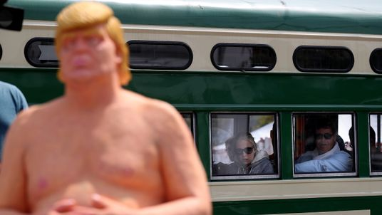 Train passengers look at a statue depicting republican presidential nominee Donald Trump in San Francisco