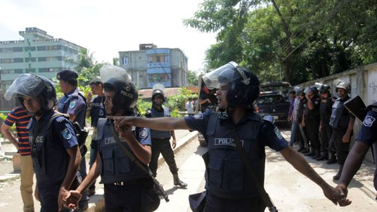 Police officers stand guard near the militant hideout in Narayanganj