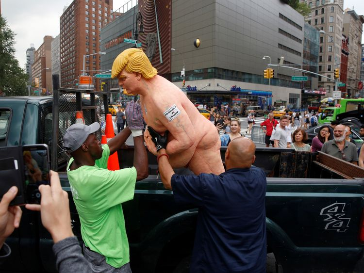 New York City Parks workers place a naked statue of U.S. Republican presidential nominee Donald Trump that was left in Union Square Park onto a truck