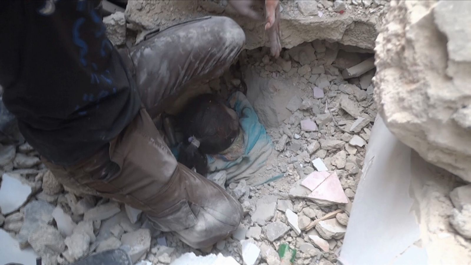 A young Syrian girl trapped in the rubble of a building in Aleppo