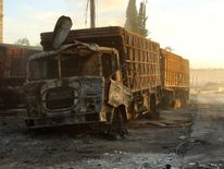 Damaged aid trucks after an airstrike on the rebel held Urm al-Kubra town, western Aleppo city, Syria