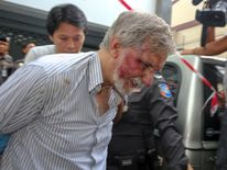 A foreign member of a suspected passport forgery gang is escorted by police officers after a raid in Bangkok
