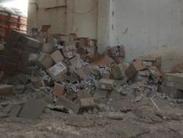 Damaged Red Cross and Red Crescent medical supplies lie inside a warehouse after an airstrike
