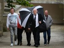 Claire Riley, 23, (behind umbrella) arrives at Northampton Crown Court to be sentenced