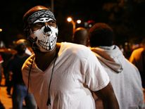 A masked protester walks in the streets downtown during another night of protests over the police shooting of Keith Scott in Charlotte, North Carolina