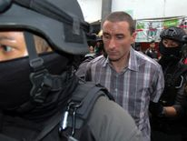 A foreign member of a suspected passport forgery gang is escorted by police officers