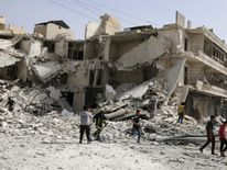 People inspect a damaged site after airstrikes in Aleppo