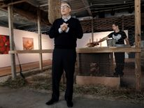 Bill Gates stands in front of a chicken coop in New York, where he pledged to donate 100,000 chicks to developing countries