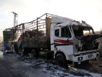 A damaged truck carrying aid is seen on the side of the road in the town of Orum al-Kubra on the western outskirts of the northern Syrian city of Aleppo