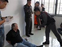 A foreign member of a suspected passport forgery gang is detained by police officers