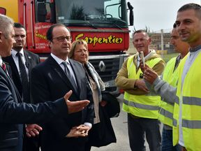 French President Francois Hollande (C) listens to David Fagnard (L), the CEO of Carpentier transport company next to mayor of Calais Natacha Bouchart (C-R) during a visit to the Carpentier's premises on September 26, 2016 as part of his visit to Calais, northern France. French President Francois Hollande said on a visit to the port of Calais today that the sprawling 'Jungle' migrant camp there would be 'completely dismantled'. Hollande visits Calais, the northern French port which is home to the