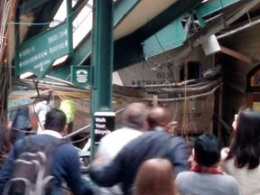 Onlookers view a New Jersey Transit train that derailed and crashed through the station in Hoboken, New Jersey