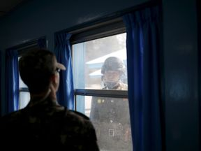 North (R) and South Korean soldiers look at each other through a window of a conference room in the United Nations Command Military Armistice Commission Conference Building at the truce village of Panmunjom, South Korea, March 30, 2016. REUTERS/Kim Hong-Ji