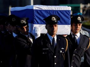 The flag-draped coffin of former Israeli president Shimon Peres is carried by members of a parliamentary guard upon its arrival at the Knesset Plaza in Jerusalem