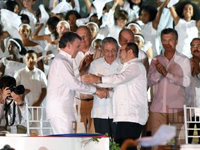 Colombian President Juan Manuel Santos (L at centre) and the leader of the FARC, Rodrigo Londono (R at centre)-- better known by his nom de guerre, Timoleon 'Timochenko' Jimenez congratulate each other signing the historic peace agreement between the Colombian government and the Revolutionary Armed Forces of Colombia (FARC), in Cartagena, Colombia