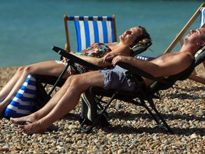 A couple enjoying the hot weather on the beach in Brighton, East Sussex