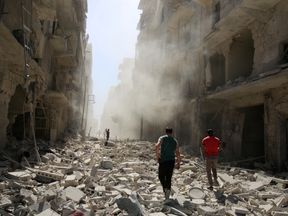 Residents inspect the damage after an airstrike in al Qaterji, Aleppo