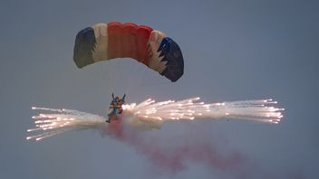 A parachutist releases fireworks for an aerial display