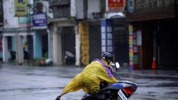 A motorcyclist falls whilst riding along a road in Hualien