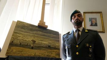 An Italian policeman stands next to The Beach At Scheveningen During A Storm, a Van Gogh painting stolen 14 years ago and found in Italy