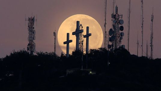 The full moon is seen behind the hill of the three crosses in Cali, Colombia
