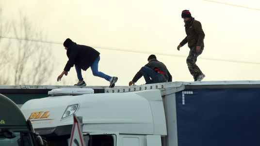 Migrants on the roof of a lorry in Calais. File picture
