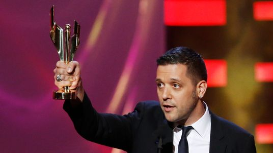 George Stroumboulopoulos holds an award