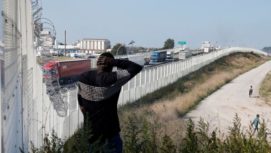 A migrant walks past the fence which secures the approach to the city from migrants trying to reach Britain, in Calais, France